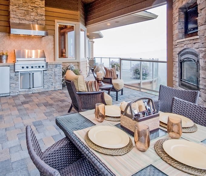 Deck with outdoor kitchen and dining space with fireplace